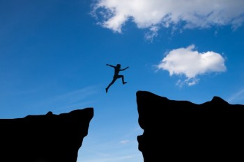 man-jump-through-the-gap-between-hill-man-jumping-over-cliff-on-sunset-background-business-concept-idea_1323-99